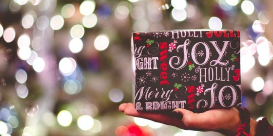 Eine Hand hält ein Weihnachtsgeschenk.